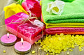 Two bars homemade soap towels bath salts two candles tulips background old wooden boards Stock Image