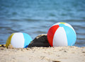 Two beach balls in sand on sea Royalty Free Stock Photo