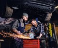 Two b mechanics working with an angle grinder in a garage. Royalty Free Stock Photo