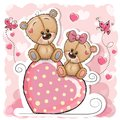 Two Bears is sitting on a heart on a pink background