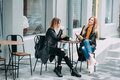 Two beautiful attractive stylish women are sitting outdoor in cafe drinking coffe and tea talking and enjoying great day. Royalty Free Stock Photo