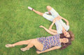 Two beautiful brunettes lying on the grass girls enjoying vintage looking picture Stock Image