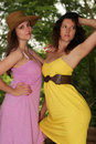 Two beautiful country girls in a outside wearing colorful dresses and a cowboy hat Royalty Free Stock Images