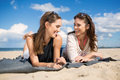 Two beautiful female friends lying on beach laughing Royalty Free Stock Photo