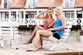 Two beautiful female friends resting on bench and pointing at camera selective focus Royalty Free Stock Photo