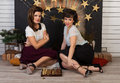 Two beautiful girl friends by the fireplace Royalty Free Stock Photo