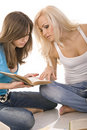 Two beautiful girl thoughtfully reading a book Royalty Free Stock Image