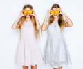 Two beautiful girlfriends having fun and indulge in fashionable dresses orange eyes closed.