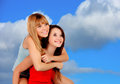 Two beautiful girlfriends on the outside with a blue sky background Royalty Free Stock Photos