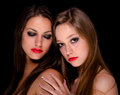 Two beautiful girls being intimate isolated on black background Stock Photos