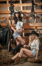 Two beautiful girls, blonde and brunette, with country look, indoors shot in stable, rustic style. Attractive women with hats