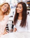 Two beautiful girls in cafe chatting summer Royalty Free Stock Photo