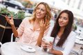 Two beautiful girls in cafe with cups chatting summer Stock Photo