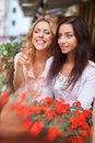 Two beautiful girls in cafe among flowers outdoors a city Stock Photography