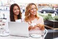 Two beautiful girls in cafe with laptop cups and summer Stock Photography