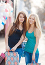 Two beautiful girls with colorful shopping bags young women in t shirts and jeans multi colored in their hands on a sunny summer Royalty Free Stock Photography
