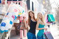 Two beautiful girls with colorful shopping bags young women in t shirts and jeans multi colored in their hands on a sunny summer Stock Photography
