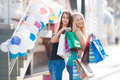 Two beautiful girls with colorful shopping bags young women in t shirts and jeans multi colored in their hands on a sunny summer Royalty Free Stock Photos