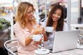 Two beautiful girls cups and laptop in summer cafe Stock Photos