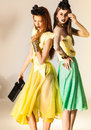 Two beautiful girls dressed in summer dresses studio shot Stock Photos