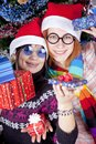 Two beautiful girls with gifts in christmas hats Royalty Free Stock Photos