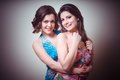 Two beautiful girls on gray background Royalty Free Stock Photo
