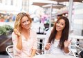 Two beautiful girls with laptop chatting in summer cafe Stock Photography