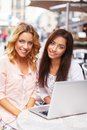 Two beautiful girls with laptop in summer cafe Stock Photo