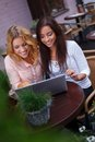 Two beautiful girls with laptop in summer cafe Royalty Free Stock Photo