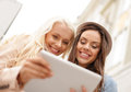 Two beautiful girls looking into tablet pc holidays technology and tourism concept toursits in the city Stock Photos