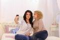 Two beautiful girls make selfie photo, using gadget, for memory,