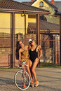 Two beautiful girls posing near a vintage bike Royalty Free Stock Photo