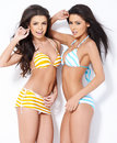 Two beautiful girls posing in swimsuits while on white background Stock Image