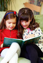 Two beautiful girls reading book at home Stock Photography