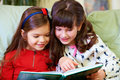 Two beautiful girls reading book at home Stock Images