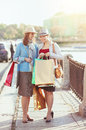 Two beautiful girls with shopping bags in the city Stock Photos