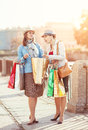 Two beautiful girls with shopping bags in the city Stock Images