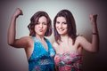Two beautiful girls showing muscle on gray background Royalty Free Stock Images