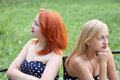 Two beautiful girls take offense at each other sit on bench and in park summer day Royalty Free Stock Images