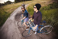 Two beautiful hipsters standing outdoor in summer with white vintage fixed gear bicycle Royalty Free Stock Photography