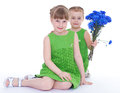 Two beautiful little girl with a bouquet of blue flowers Stock Photos