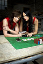 Two beautiful mafia ladies with guns pretty in role play both are standing beside a poker table cards and chips Royalty Free Stock Image