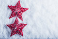 Two Beautiful magical vintage red stars on a white snow background. Winter and Christmas concept Royalty Free Stock Photo