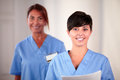 Two beautiful nurse looking and smiling at you portrait of on blue uniform while standing holding documents Royalty Free Stock Images