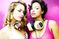 Two beautiful sexy disco women in a bar lounge with headphones Stock Images
