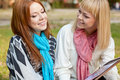 Two beautiful sisters with photo album in the park Royalty Free Stock Photography