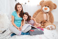 Two beautiful smiling sisters sitting in children room Royalty Free Stock Photo