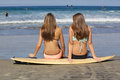 Two Beautiful Teenage Girls sitting on a Surf board in the sand at the beach Royalty Free Stock Photo