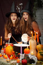 Two beautiful witches brew the potion in the boiler Royalty Free Stock Photography