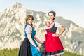 Two beautiful woman in the alps women with traditional austrian clothes Royalty Free Stock Photo